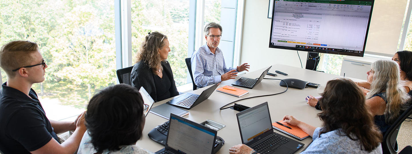 Staff from Gift Accounting meeting in a bright conference room, projecting an excel document on monitor