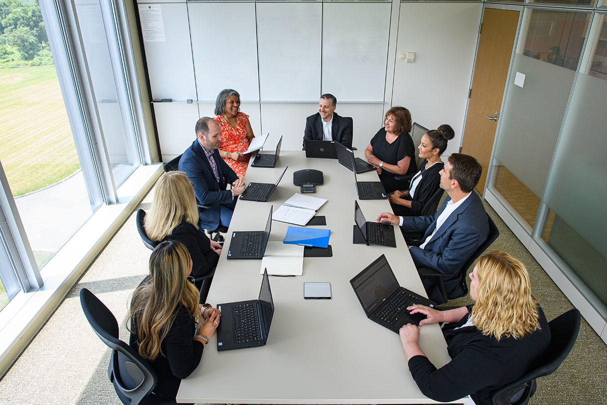 A diverse group of nine staff from Financial Services meet in a conference room.