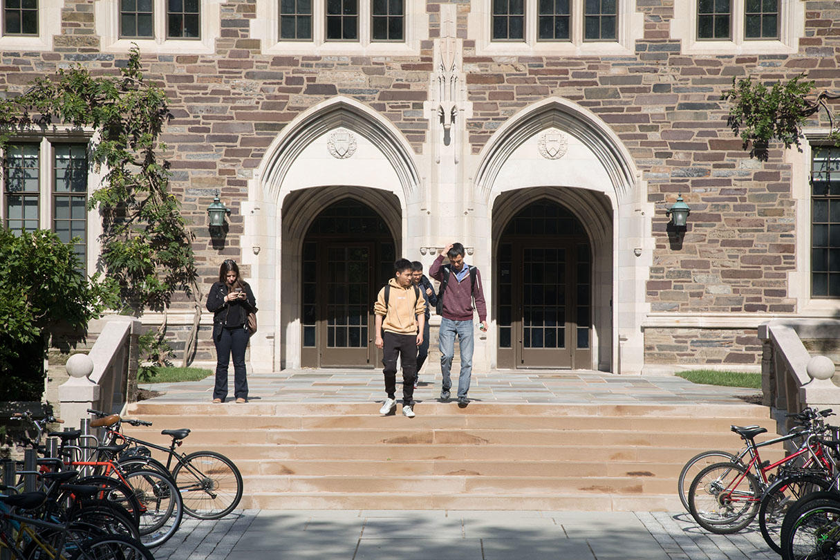 Students walking down a stone stairway, outside of a stone building with arches. Bikes adorn both sides of the path.